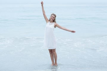 Smiling blonde in white dress standing by the sea