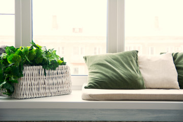Pillows on the windowsill and plastic window. Wicker basket with