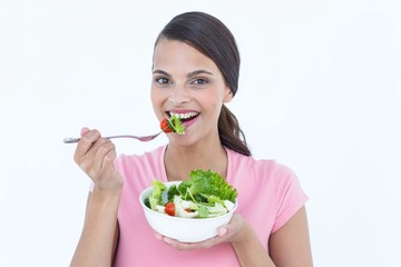 Pretty brunette eating a bowl of salad