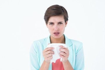 Sick woman holding a tissue and looking at camera