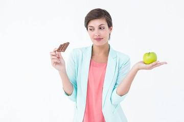 Brunette choosing between an apple and chocolate bar
