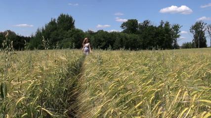 beautiful pregnant woman walk through ripe rye field in summer
