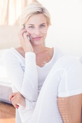 Smiling blonde woman calling on the phone