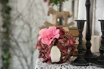 Designer composition with artificial and dried flowers.