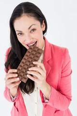 Smiling brunette biting bar of chocolate