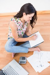 Pretty brunette writing on a paper while calculating