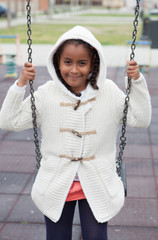 Outdoor portrait of a cute young black girl playing with a swing