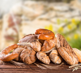Variety of bread on wooden table with nature background