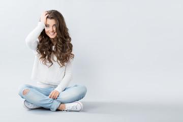 Beautiful girl sitting on the floor cross-legged.