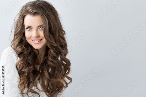 Fototapeta Portrait of a beautiful young woman with wavy hair.