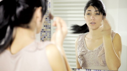 Beautiful happy young lady putting makeup in front of mirror
