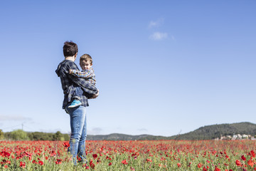 Mother and her little child having fun in a field, flower in for