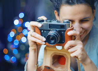 Smiling woman photographed retro camera.