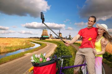 Couple taking Selfie against windmills near Amsterdam