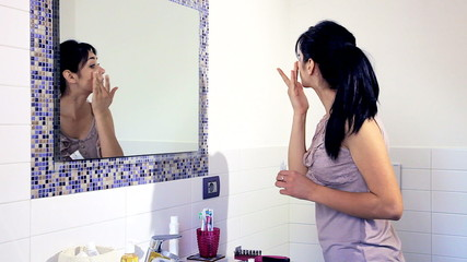 Happy young woman putting makeup in bathroom at home