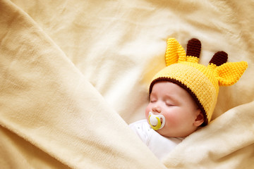 Baby sleeping in giraffe hat