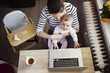 Young mother in home office with computer and her daugher - 81913033