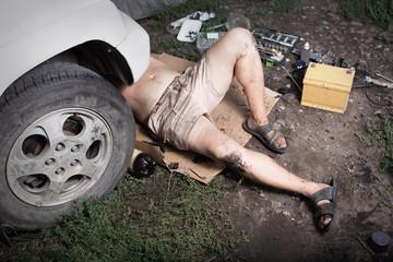 Mechanic lying and working