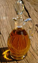 Glaskaraffe mit Olivenöl vor rustikalem Hintergrund