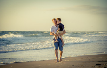 young happy father holding little son walking on beach sand
