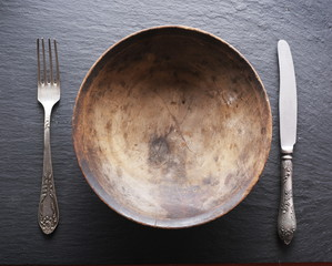 Silver cutlery and old wooden plate on a grey background.