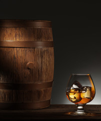 Glass of matured whiskey and old wooden barrel.
