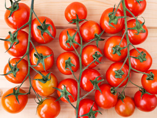 Three tomato bunches on the wooden background