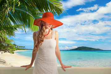 Pretty woman in white dress on balcony