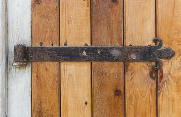 Old wooden door with an old cast iron door hinges