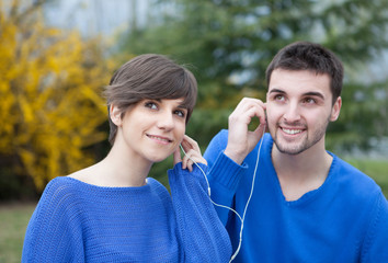 Lovers in the park listening to music with headphones