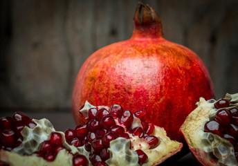 red juicy pomegranatedark rustic wooden table