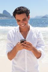 Junger Mann schreibt eine SMS an der Copacabana