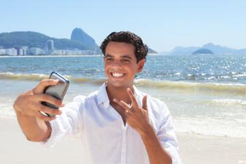 Fröhlicher junger Mann macht ein Selfie an der Copacabana