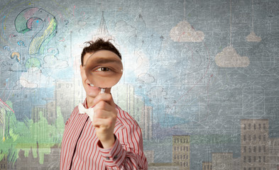 Guy looking in magnifying glass