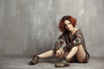 girl in a big, knitted sweater and boots sitting on a gray backg