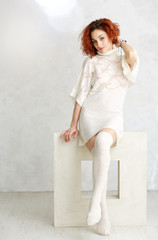redhead curly girl in a white knitted sweater and stockings sitt