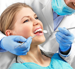 Dental health. Male dentist curing a female patient