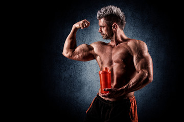 young handsome man with strong muscles, protein drink after trai