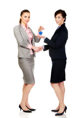 Businesswoman giving a key to her partner.