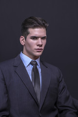 Young businessman posing in suit on a black background