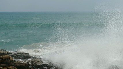 big waves crashing on stone beach 4k