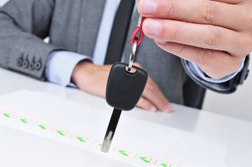 man in office giving a car key