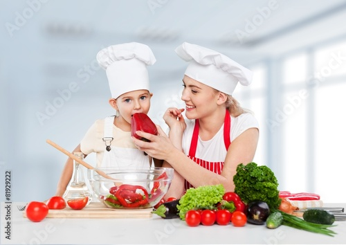 Adorable. Mother feeding kid daughter vegetables in kitchen