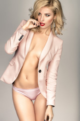 Blonde young woman in pastel lingerie and jacket