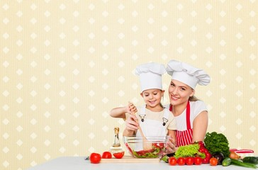 Adorable. Mother teaching kid daughter mixing salad at kitchen