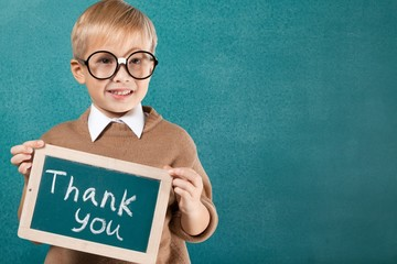 Sign. Child holding a thank you sign standing against white
