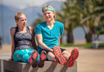 Two young people rest together on the bench after jogging