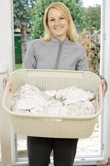 Frau mit Wäschekorb voller Schmutzwäsche