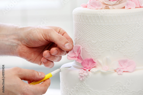 Fotobehang Bakkerij Confectioner decorates wedding cake