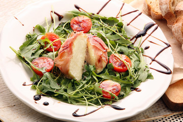 Mozzarella baked in ham of Parma with arugula spring salad